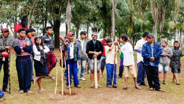 With protection totems in the ground, Kaiowa tribe members prepare for an assembly.