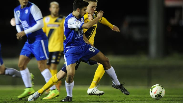 Canberra Olympic's Jordan Tsekenis and Adam Berry from the Central Coast Mariners fight for possession in last night's pre-season friendly at Gungahlin Enclosed Oval.