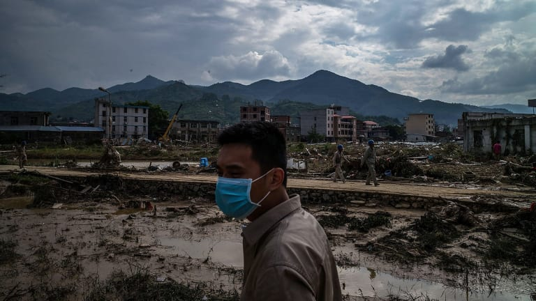 A man stands in front of the damaged village at Bandong Town.
