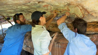 Researchers Nick Sundblom, Helen Green and Jordy Grinpukel remove tiny mineral accretions from a rock art panel motif in the Kimberley. Courtesy of Kimberley Foundation Australia.