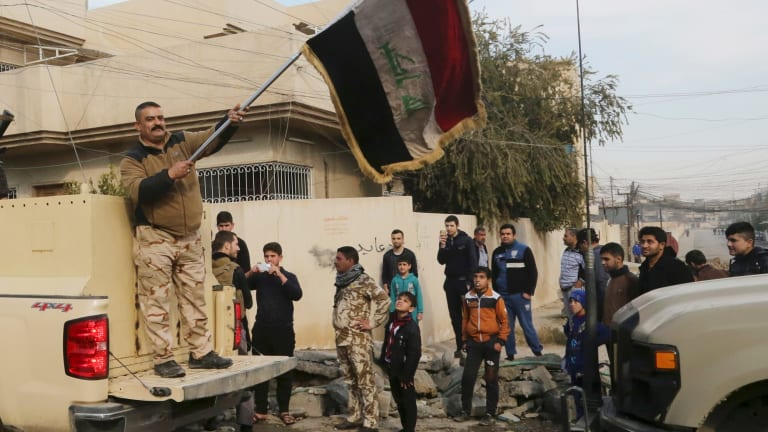 An Iraqi soldier waves the national flag as security forces patrol on the eastern side of Mosul, Iraq.