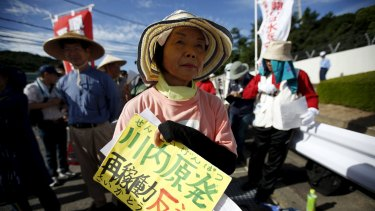 A protester attends a rally against the restarting of the plant at an entrance gate of Kyushu Electric Power's Sendai nuclear power station.