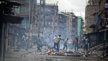 A protester throws an unexploded tear gas grenade back to the police, during clashes in the Mathare area of Nairobi.