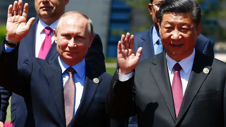 Chinese President Xi Jinping, right, and Russian President Vladimir Putin wave at the Belt and Road Forum on Yanqi Lake just outside Beijing on Monday.