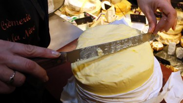 A woman cuts a slice of butter on a market in Bayonne, south-western France.