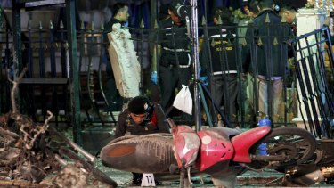 Experts investigate the remains of destroyed motorcycles at the Erawan shrine.