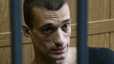 Russian artist Pyotr Pavlensky sits in a cage in court room in Moscow.