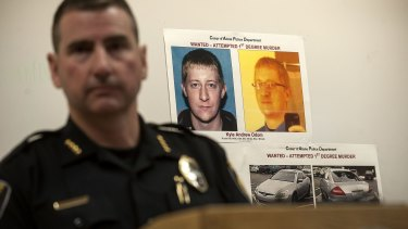 Coeur d'Alene Police Chief Lee White speaks during a news conference on Monday with a photo of Kyle Andrew Odom in the background.