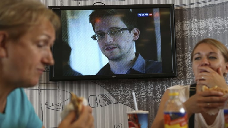 Passengers eat at a cafe with a TV screen showing a news program report on Snowden, in the background, at Sheremetyevo airport in Moscow.