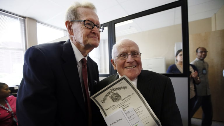 Jack Evans, 84, left, and George Harris, 82, right, show their marriage licence after being the first couple to receive it from the Dallas County Clerk.