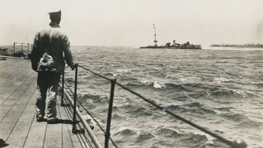 An unidentified seaman on the quarter deck of HMAS Sydney looks at the wrecked German cruiser Emden
