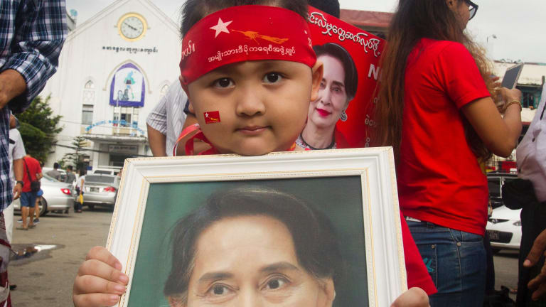 A boy holds a portrait of Myanmar's State Counsellor Aung San Suu Kyi during a rally to show support for her in Yangon.