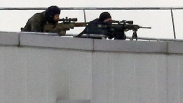 Before the assault ... French special forces take position with sniper rifles on the rooftop of a complex at an industrial building in Dammartin-en-Goele, northeast of Paris.