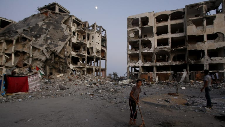 A Palestinian plays in a courtyard near destroyed buildings at a residential neighbourhood in Beit Lahiya, northern Gaza Strip, in August 2014.