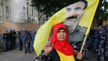 A Kurdish demonstrator holds a flag with a portrait of jailed Kurdish leader Abdullah Ocalan, during a protest against the operation by the Turkish army, outside the Russian embassy in Beirut.