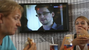 Passengers eat at a cafe with news report on Edward Snowden in the background at Sheremetyevo airport in Moscow in 2013.
