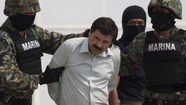 Guzman is escorted to a helicopter in handcuffs after being captured in Mexico City in February 2014.