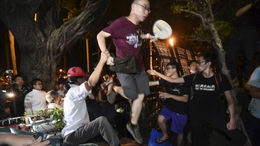 Protesters climb over a barricade to enter the Ministry of Education in Taipei.