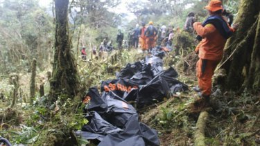 A rescue team member stands near bodies of the victims of the crashed Trigana Air plane, at the crash site near Oksibil, Bintang Mountains district, Papua province, Indonesia, in August.