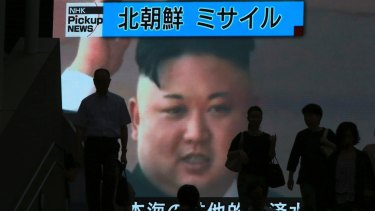 People walk past a giant TV screen showing North Korean leader Kim Jong-un celebrating the country's latest missile test launch.