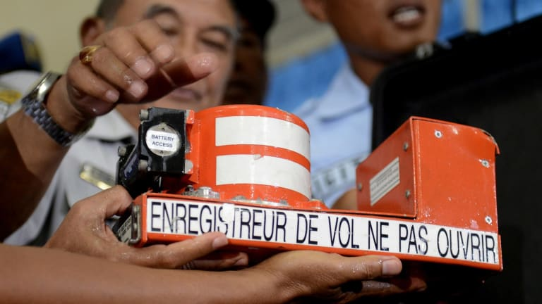 Indonesian soldiers hold the cockpit voice recorder of AirAsia QZ8501.