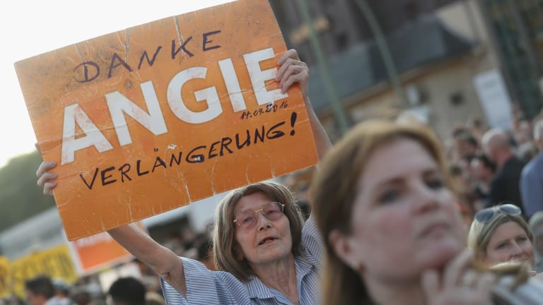 "A supporter of the German Christian Democrats holds up a sign that reads: ""Thanks Angie, keep going!"" in reference to German Chancellor Angela Merkel."
