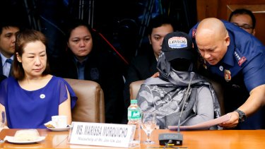 Philippines National Police Chief Ronald dela Rosa, right, shows Marissa Morquicho documents at the start of the probe. The head of the unit accused in the case has been linked to the police chief.