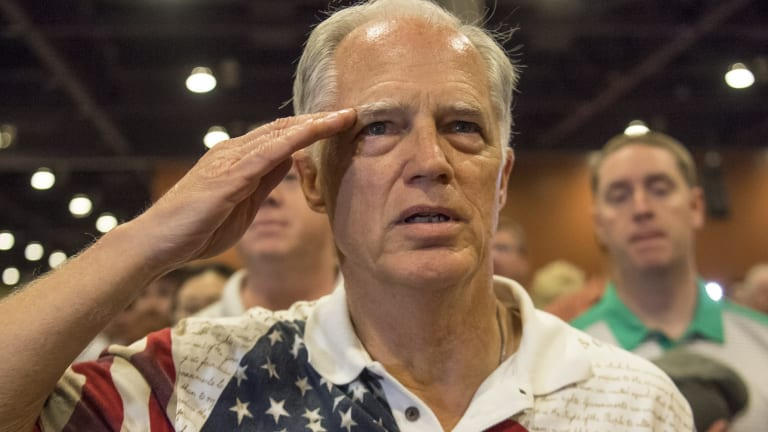 An attendee salutes as the pledge of allegiance is recited at a Donald Trump event.