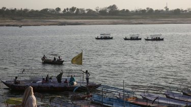 Indians ride on boats in the River Ganges.