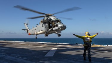 A Seasprite helicopter lands on HMAS Canberra's flight deck during the Talisman Sabre military drills.