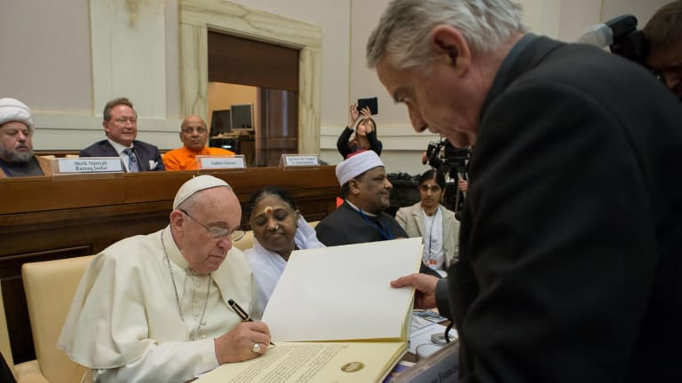 Signing up: Pope Francis signs a joint Declaration of Religious Leaders against Modern Slavery as Andrew Forrest watches on.