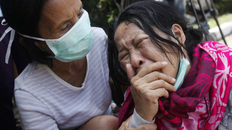 Family members of passengers on a military plane that crashed onto a residential area weep at a hospital in Medan, North Sumatra, in June, 2015.