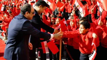 Egyptian President Abdel-Fattah el-Sissi, left, and Chinese President Xi Jinping, shake hands with children at the Presidential Palace in Cairo, Egypt on Thursday. Jinping is on a two-day visit to the country.