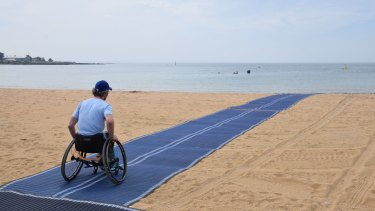 Brook Quinn tests the wheelchair-accessible matting at Williamstown Beach.