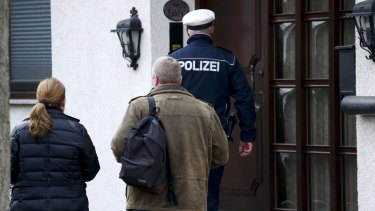 A German police officer and unidentified people prepare to enter a house believed to belong to crashed Germanwings flight 4U 9524 co-pilot Andreas Lubitz in Montabaur, Germany