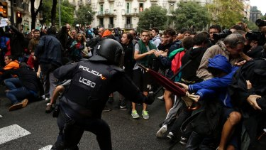 A Spanish National Police officer clashes with pro-referendum supporters in Barcelona on Sunday.