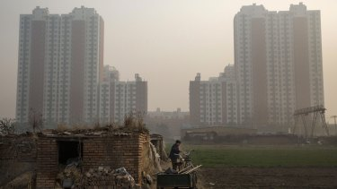 An elderly Chinese farmer stands outside her home near a housing development in Hebei province just outside Beijing.