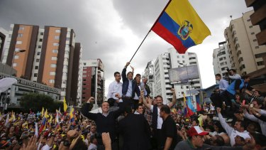 Presidential candidate Guillermo Lasso waves an Ecuadorean national flag in Quito on Tuesday. He has vowed to eject Julian Assange if he wins.