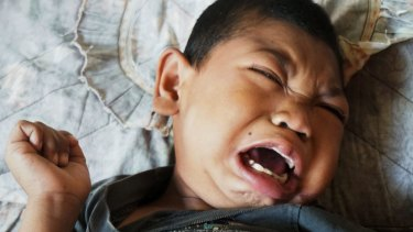 Muhammad Fikri, aged eight, suffers from severe mental and physical disabilities.