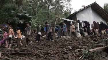 Villagers walk through an area affected by landslides in Banjarnegara, Java, on Sunday.