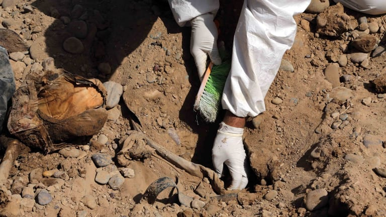 An Iraqi forensic worker excavates human remains in a mass grave, believed to contain the bodies of Iraqi soldiers killed by Islamic State militants when they overran Camp Speicher military base last June, in Tikrit.