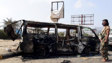 Fighting continues: A man stands by the wreckage of a van hit by an air strike in Yemen's southern port city of Aden.