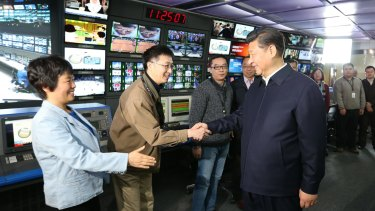 Propaganda offensive ... In this photo released by China's Xinhua News Agency, Chinese President Xi Jinping, right, shakes hands with staff members at the control room of China Central Television (CCTV) in Beijing on Friday.