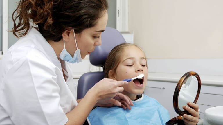A dentist shows a child how to brush her teeth.