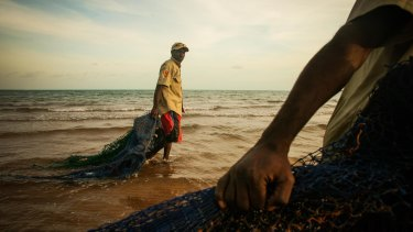 Ranger Dukpirri Marwali pulls ghost nets discarded from fishing boats ashore in the Laynhapuy Indigenous Protected Area at Yilpara on the Arnhem Land coast, NT.