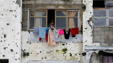 A Palestinian woman hangs clothes outside her apartment in the Gaza Strip. The building was partially destroyed during the 2014 Israeli bombardment of the besieged enclave.