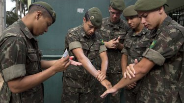 Army soldiers apply insect repellent as they prepare for a clean-up operation against the Aedes aegypti mosquito in Sao Paulo.