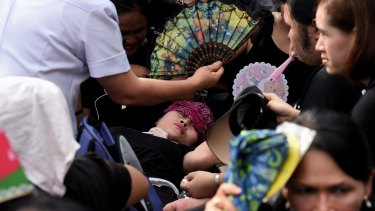 A woman faints outside the Grand Palace in Bangkok waiting for the body of the king.