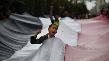 A boy chants slogans through a gap in a national flag raised by Shiite rebels, known as Houthis, during a protest against Saudi-led airstrikes in Sanaa on Friday.