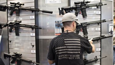 An attendee looks over rifles in the ArmaLite booth at the 144th National Rifle Association (NRA) annual meetings in Nashville in April.